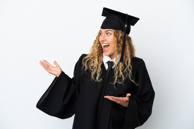 Młody absolwent uniwersytetu na białym tle z wyrazem zaskoczenia, patrząc z boku