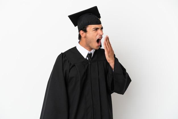 Młody absolwent uniwersytetu na białym tle ziewa i zakrywa ręką szeroko otwarte usta