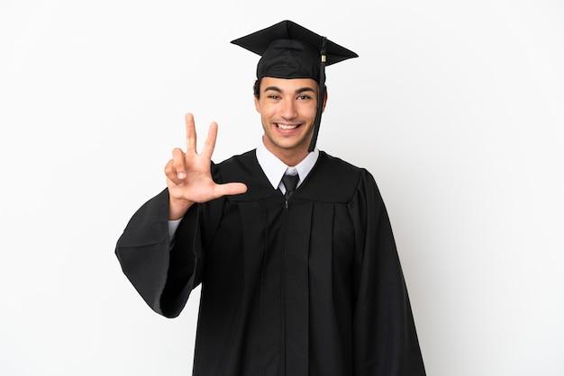 Młody absolwent uniwersytetu na izolowanym białym tle szczęśliwy i liczący trzy palcami