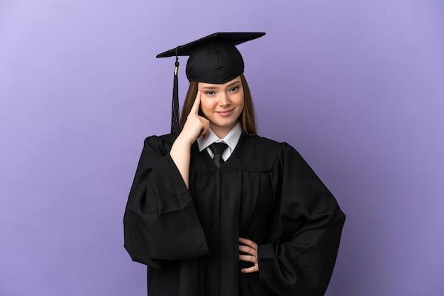 Młody absolwent uniwersytetu na odosobnionym fioletowym tle myśli o pomyśle