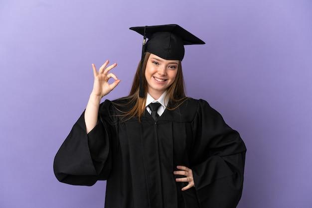 Młody absolwent uniwersytetu na odosobnionym fioletowym tle pokazującym znak ok palcami