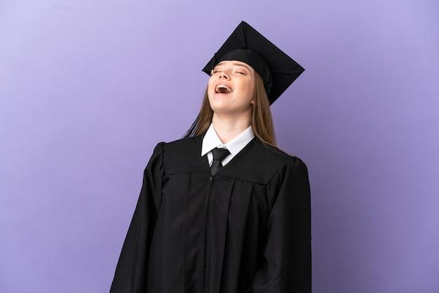 Młody absolwent uniwersytetu na odosobnionym fioletowym tle śmiejąc się