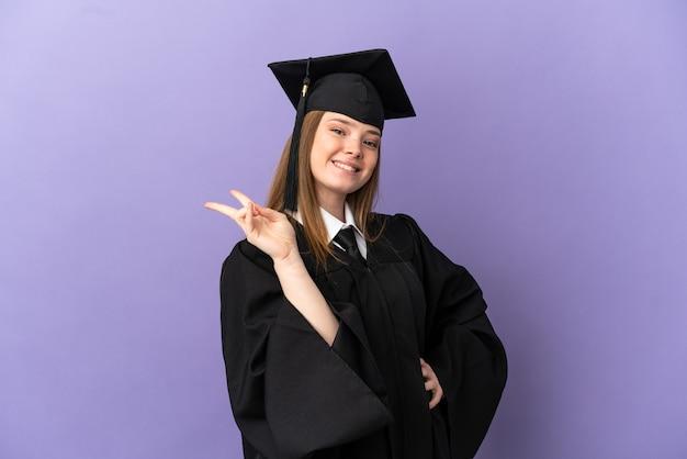 Młody absolwent uniwersytetu na odosobnionym fioletowym tle uśmiechający się i pokazujący znak zwycięstwa