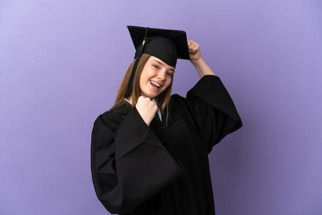 Młody absolwent uniwersytetu świętujący zwycięstwo na odosobnionym fioletowym tle
