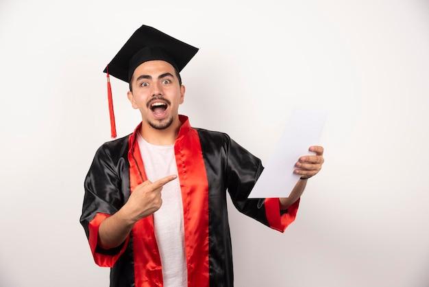 Młody absolwent w sukni, wskazując papier na białym tle.
