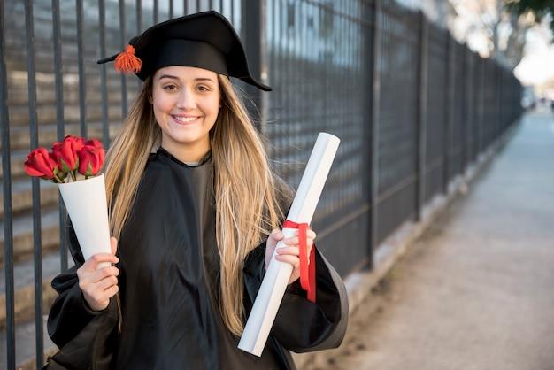 Młody absolwent z bukietem róż