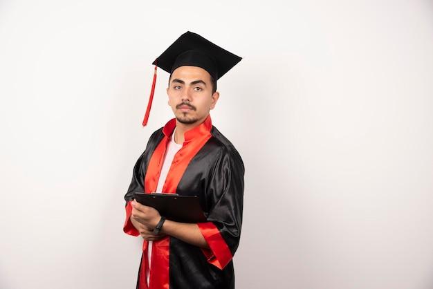 Młody absolwent z dyplomem na białym tle.