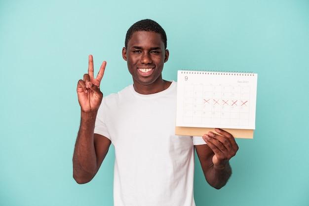 Młody african american człowiek posiadający kalendarz na białym tle na niebieskim tle, pokazując numer dwa palcami.