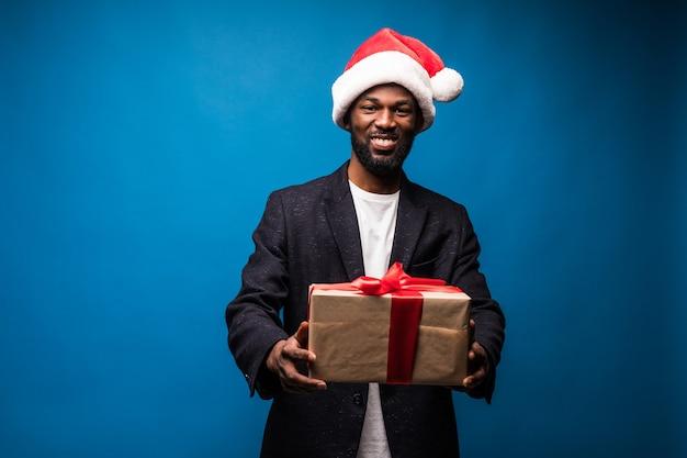 Młody african american człowiek ubrany w kapelusz santa oferujący prezent