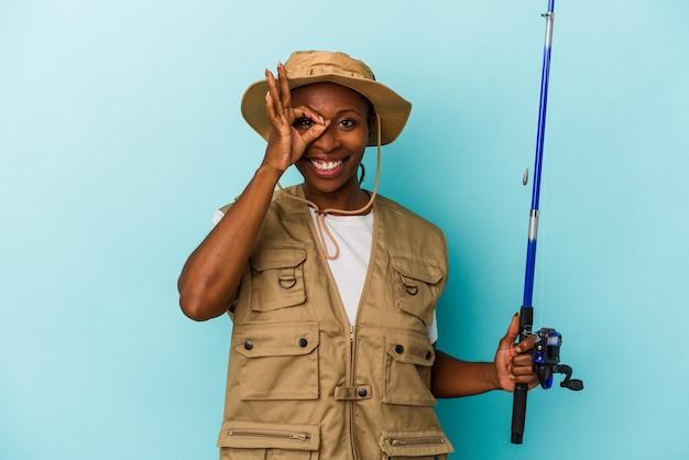 Młody african american fisherwoman trzymając pręt na białym tle na niebieskim tle podekscytowany, zachowując ok gest na oko.