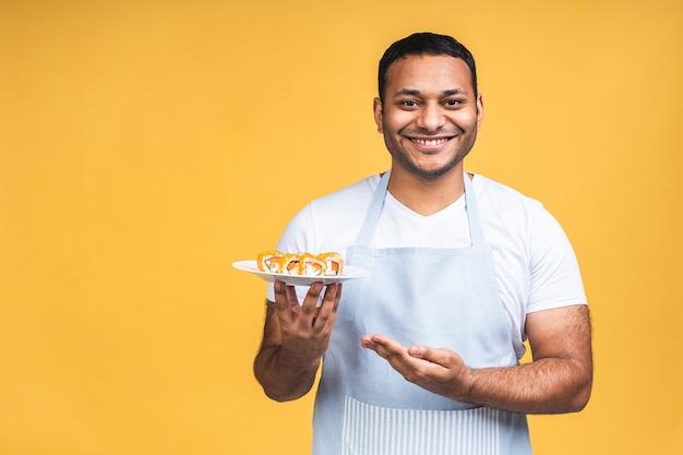 Młody african american indian czarny człowiek jedzenie sushi za pomocą pałeczek na na białym tle żółty. gotuj przygotowując sushi.