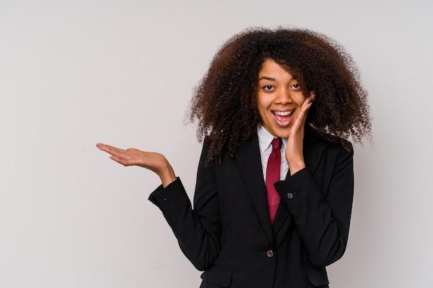 Młody african american kobieta biznesu ubrana w garnitur na białej ścianie posiada kopię miejsca na dłoni, trzymaj rękę na policzku. zdziwiony i zachwycony.