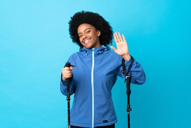 Młody african american z plecakiem i kijkami trekkingowymi na białym tle na niebiesko salutując ręką z happy wypowiedzi