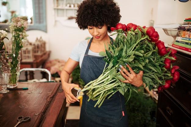 Młody afro afrykański kobieta tnący trzon czerwoni kwiaty