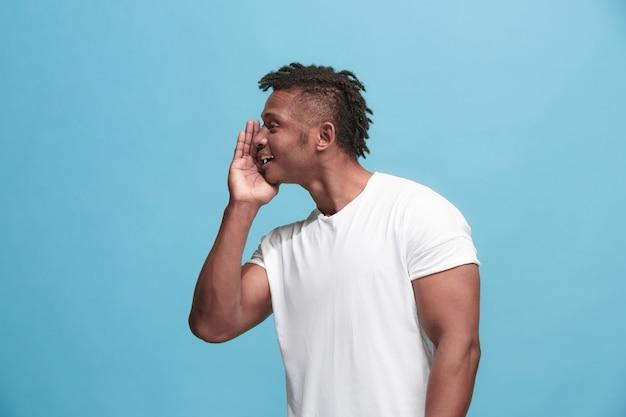 Młody afro-amerykanin szepcze tajemnicę za ręką na niebieskim tle