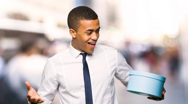 Młody afro amerykański biznesmen przytrzymanie pudełko w ręce w mieście