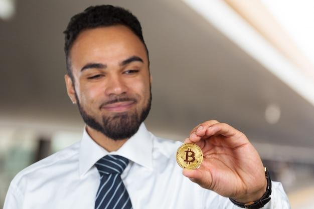 Młody afro amerykański człowiek z bitcoinem w ręku