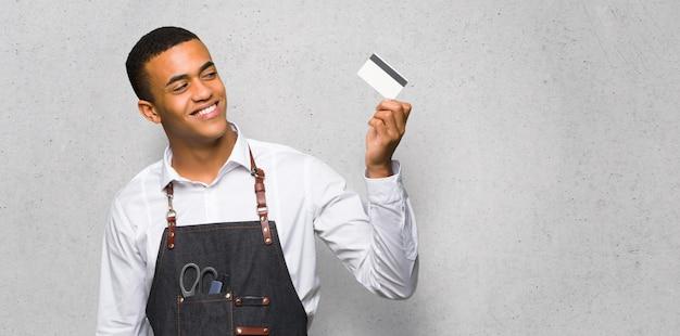 Młody afro amerykański fryzjer człowiek posiadający kartę kredytową i myślenia na teksturą ściany
