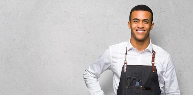 Młody afro amerykański fryzjer mężczyzna pozowanie z rękami w biodrze i uśmiechnięty