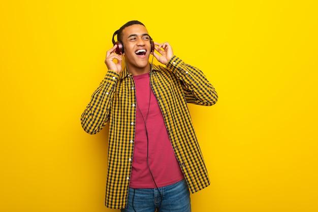 Młody afro amerykański mężczyzna słucha muzyka w hełmofonach na kolor żółty ścianie