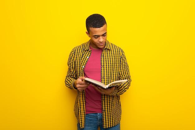 Młody afro amerykański mężczyzna trzyma książkę i cieszy się czytanie