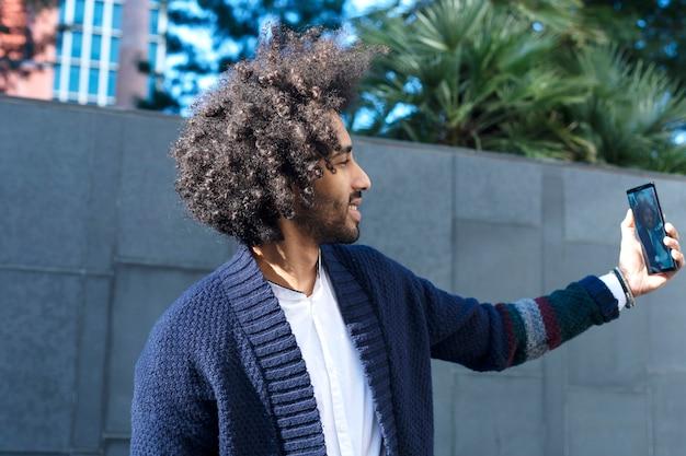 Młody afro amerykański mężczyzna uśmiecha się szczęśliwego bierze selfie autoportretu obrazek z telefonem komórkowym