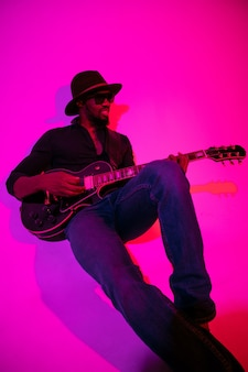 Młody afro-amerykański muzyk grający na gitarze jak gwiazda rocka na gradientowej fioletowo-różowej ścianie w świetle neonowym