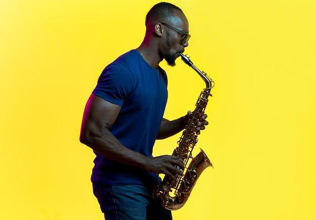 Młody afro-amerykański muzyk jazzowy grający na saksofonie na żółtym tle studio w modnym świetle neonowym. pojęcie muzyki, hobby. radosny facet improwizuje. kolorowy portret artysty.