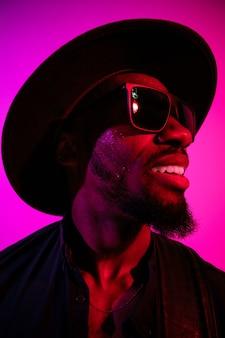 Młody afro-amerykański muzyk na gradientowej fioletowo-różowej ścianie w neonowym świetle
