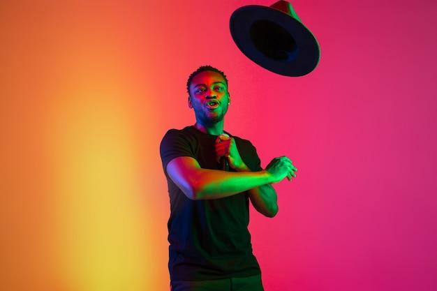 Młody afro-amerykański muzyk śpiewa na gradientowym tle pomarańczowo-fioletowym studio w świetle neonowym. pojęcie muzyki, hobby, festiwalu. radosny gospodarz imprezy, stań wyżej. kolorowy portret artysty.
