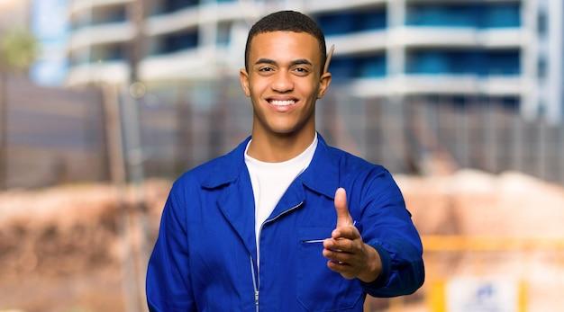 Młody afro amerykański pracownik człowiek drżenie rąk do zamknięcia dobrą ofertę na placu budowy