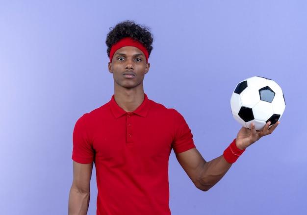 Młody afro-amerykański sportowy mężczyzna ubrany w opaskę i opaskę trzyma piłkę na bok na białym tle na niebieskiej ścianie