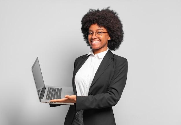 Młody afro bizneswoman uśmiecha się radośnie, czuje się szczęśliwy i pokazuje koncepcję w przestrzeni kopii z dłoni. pomysł na biznes