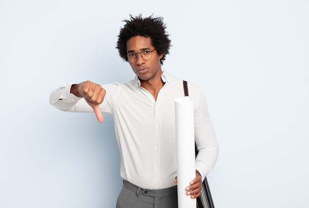 Młody afro czuje się zły, zły, zirytowany, rozczarowany lub niezadowolony, pokazując kciuki w dół z poważnym spojrzeniem