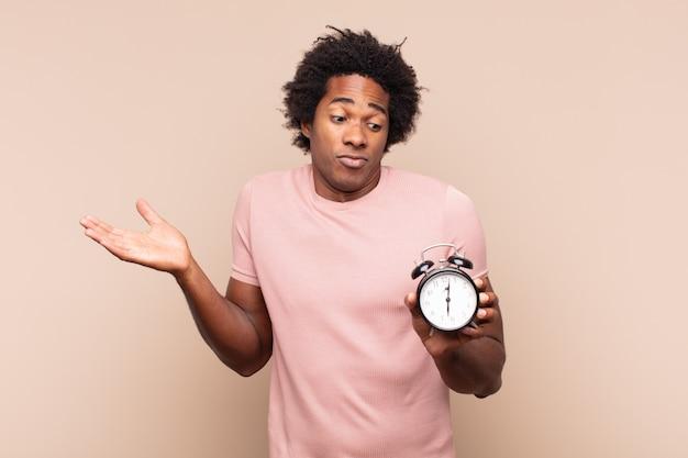 Młody afro mężczyzna czuje się zdziwiony i zdezorientowany, wątpi, waży lub wybiera różne opcje z zabawnym wyrazem twarzy