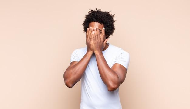 Młody afro mężczyzna czuje się zestresowany, zmartwiony, niespokojny lub przestraszony, z rękami na głowie, panikuje podczas pomyłki