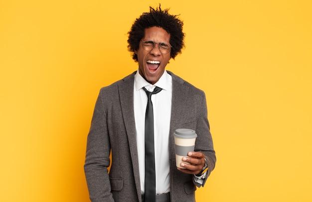 """Młody afro mężczyzna krzyczy agresywnie, wygląda na bardzo rozgniewanego, sfrustrowanego, oburzonego lub zirytowanego, krzyczy """"nie"""""""