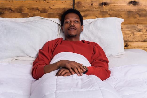 Młody afro mężczyzna relaksuje na łóżku w domu.