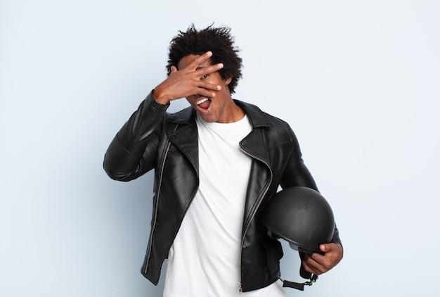 Młody afro mężczyzna wyglądający na zszokowanego, przestraszonego lub przerażonego, zakrywający twarz ręką i zerkający między palcami