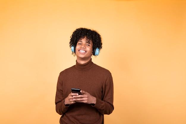 Młody afro włosy mężczyzna stojący w pozach na białym tle na żółtym tle za pomocą telefonu komórkowego, pisze wiadomości tekstowe na nowoczesnym smartfonie, ogląda śmieszne filmy w czasie wolnym