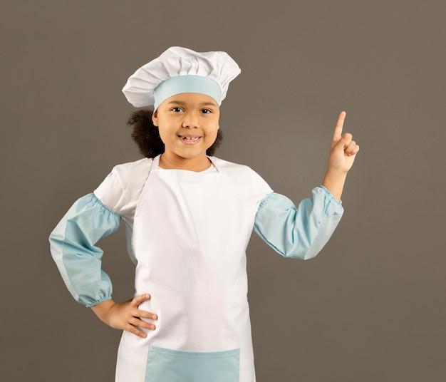 Młody afroamerican szef kuchni wskazuje w górę