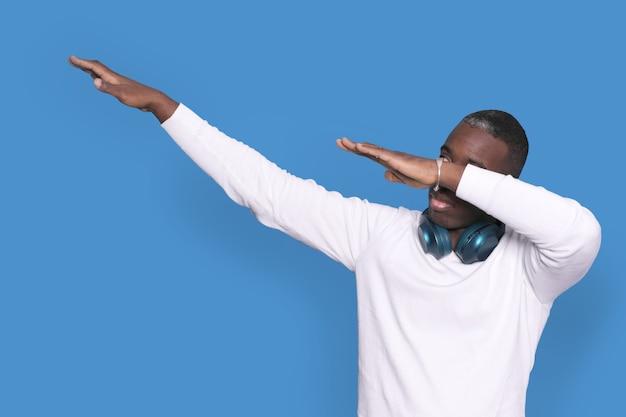 Młody afroamerykanin 20-latek ubrany w biały sweter i robiący dab hip-hopowy gest tańca, znak młodzieży ukrywa i zakrywa twarz na białym tle na jasnoniebieskim tle