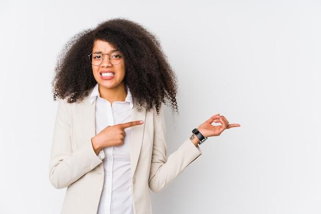 Młody afroamerykanin bizneswoman zszokowany wskazując palcami wskazującymi na miejsce.