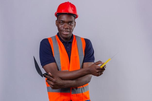 Młody afroamerykanin budowniczy mężczyzna na sobie kamizelkę budowlaną i hełm ochronny stojący z rękami skrzyżowanymi, trzymając szpachlę, patrząc pewnie