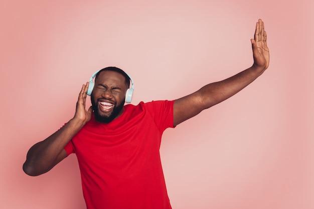 Młody afroamerykanin cieszy się muzycznym zestawem słuchawkowym na różowym tle