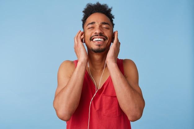 Młody afroamerykanin czuje się wspaniale i bardzo szczęśliwy, z zamkniętymi oczami i radością, słuchając w słuchawkach ulubionej piosenki, przechylając głowę i szeroko uśmiechając się odizolowany.