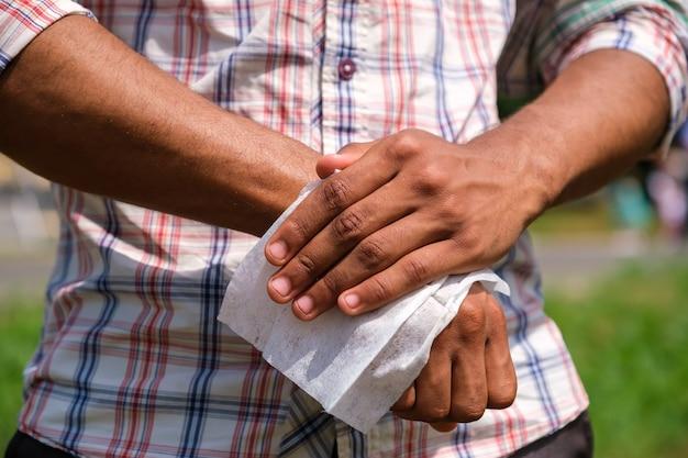Młody afroamerykanin dezynfekuje ręce z bliska na mokro na zewnątrz w parku