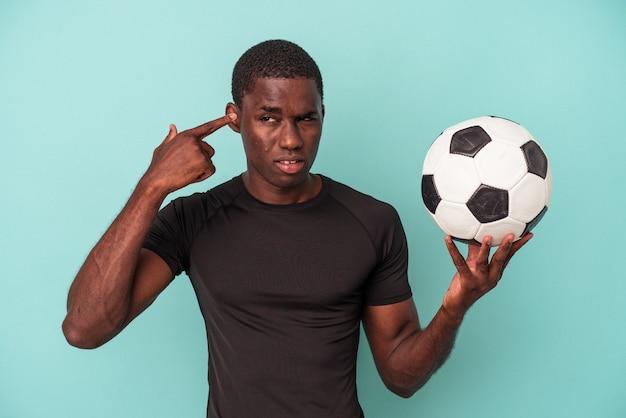 Młody afroamerykanin gra w piłkę nożną na białym tle na niebieskim tle pokazując gest rozczarowania palcem wskazującym.