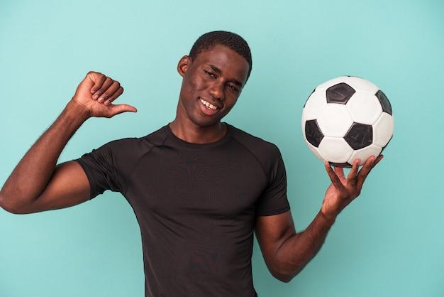 Młody afroamerykanin grający w piłkę nożną na białym tle na niebieskim tle czuje się dumny i pewny siebie, przykład do naśladowania.