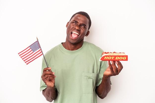 Młody afroamerykanin jedzący hot dogi i trzymający amerykańską flagę na białym tle